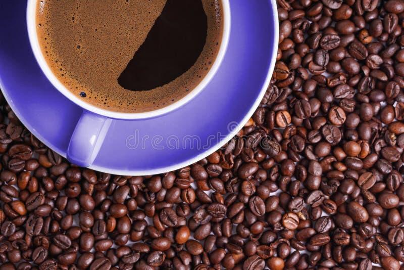 Καφές στο πορφυρό φλυτζάνι στον πίνακα που περιβάλλεται με τα φασόλια καφέ στοκ φωτογραφία