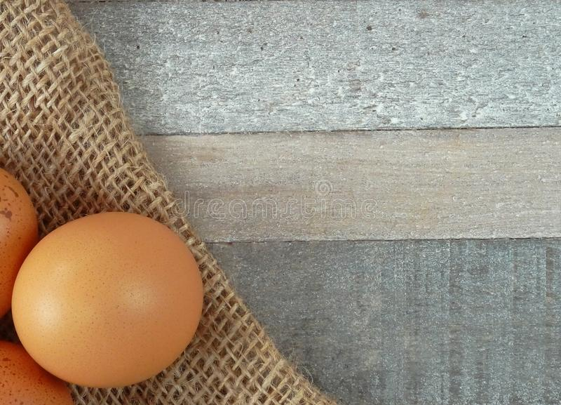 Καφετιά αυγά κοτόπουλου burlap πέρα από το ξύλινο υπόβαθρο στοκ φωτογραφία