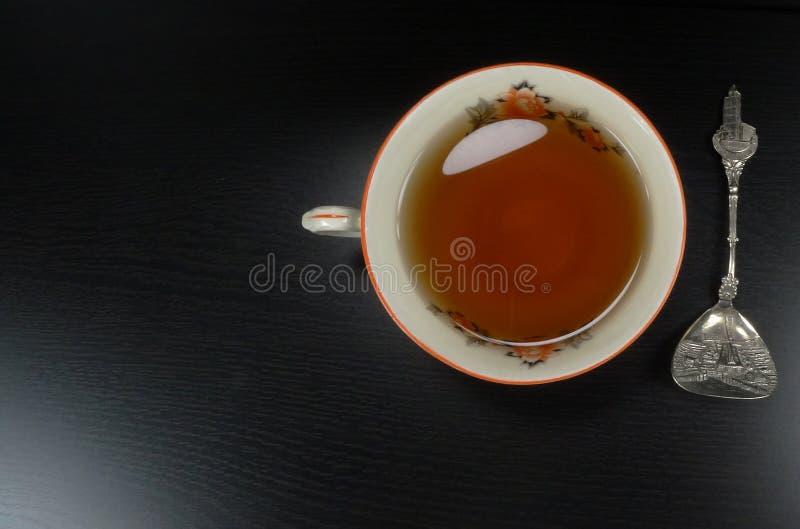 Καυτό άσπρο porselain φλυτζανιών τσαγιού με το κουτάλι, στο μαύρο ξύλινο υπόβαθρο/teatime στοκ εικόνα