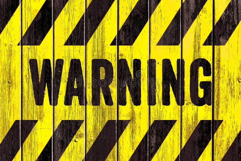 Κείμενο λέξης σημαδιών κινδύνου ΠΡΟΕΙΔΟΠΟΙΗΣΗΣ ως διάτρητο με τα κίτρινα και μαύρα λωρίδες που χρωματίζονται στο ξύλινο ευρύ υπόβ στοκ φωτογραφίες με δικαίωμα ελεύθερης χρήσης