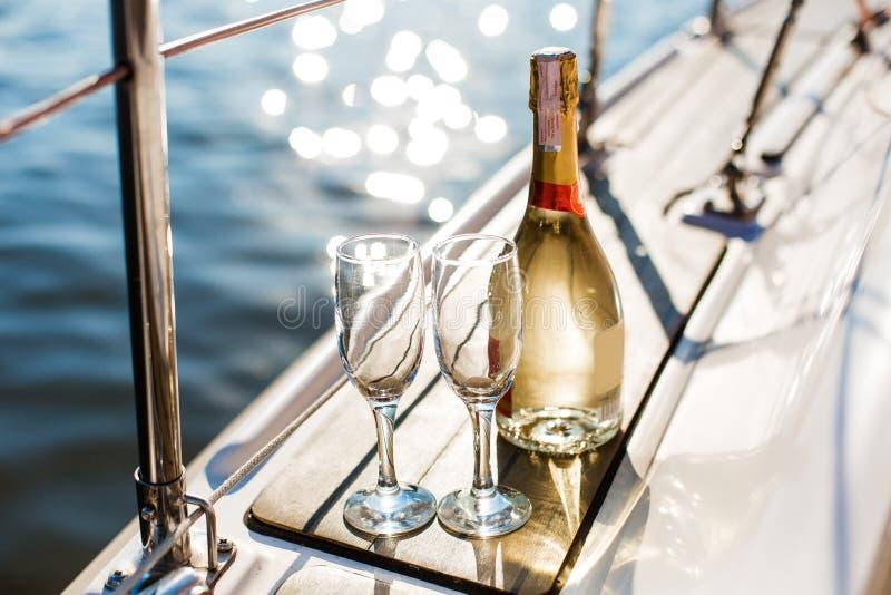 Κενά γυαλιά και μπουκάλι με τη σαμπάνια με το υπόβαθρο θάλασσας