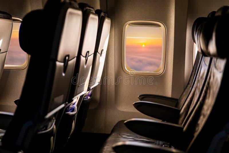 Κενά καθίσματα αεροπλάνων στην καμπίνα στο φως ηλιοβασιλέματος στοκ φωτογραφίες