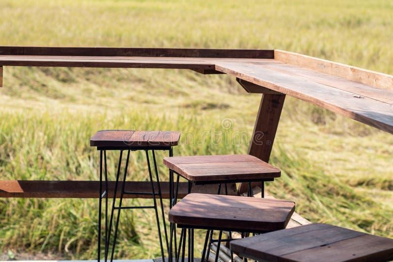 Κενή ξύλινη επιτραπέζια καρέκλα με το υπόβαθρο τοπίων της Ασίας τομέων θερινού ρυζιού άνοιξης άποψης στοκ εικόνα