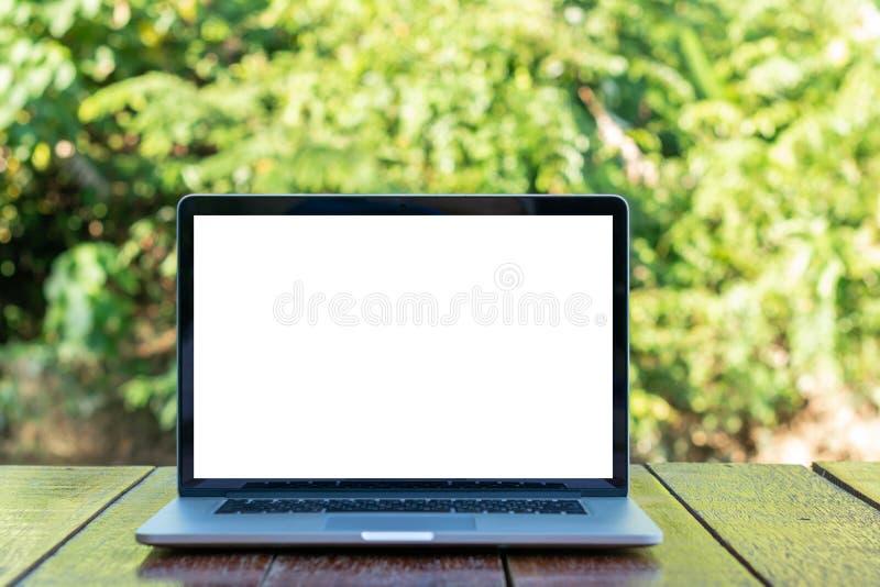 Κενή οθόνη του φορητού προσωπικού υπολογιστή στον ξύλινο πίνακα με τη θαμπάδα του δέντρου στοκ εικόνα