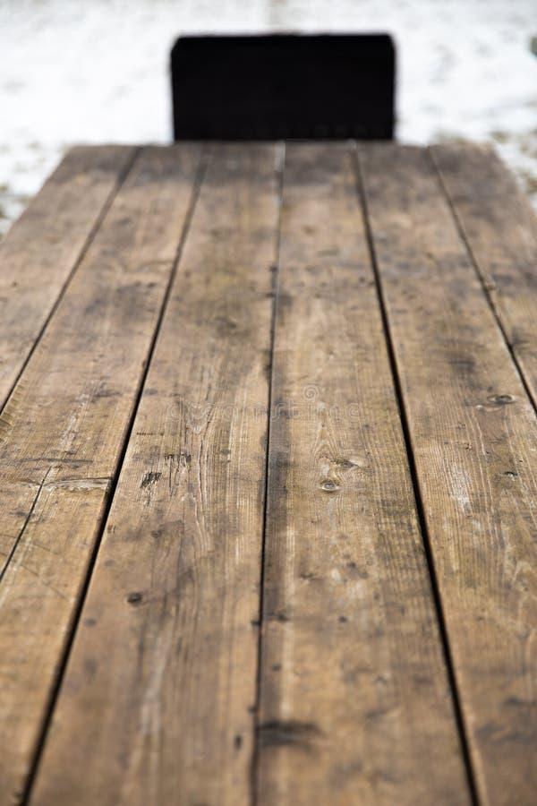 Κενός ξύλινος πίνακας με το χιόνι bokeh για έναν τομέα εστιάσεως ή μια σύσταση πικ-νίκ τροφίμων στοκ φωτογραφίες