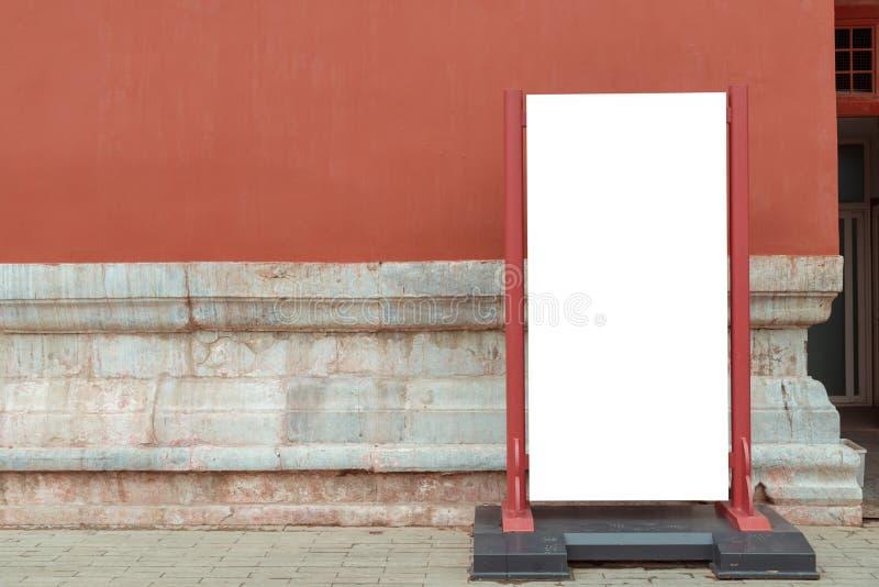 Κενός πίνακας διαφημίσεων που στέκεται μπροστά από τον κόκκινο χρωματισμένο τουβλότοιχο στοκ φωτογραφία με δικαίωμα ελεύθερης χρήσης