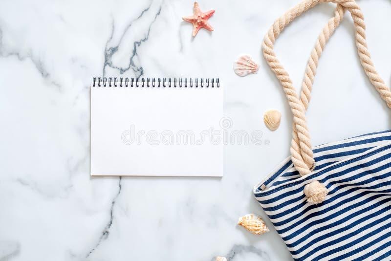 Κενό σημειωματάριο, ριγωτή θερινή τσάντα, θαλασσινά κοχύλια στο μαρμάρινο υπόβαθρο Γραφείο γυναικών του ταξιδιώτη, ομορφιά blogge στοκ εικόνα με δικαίωμα ελεύθερης χρήσης