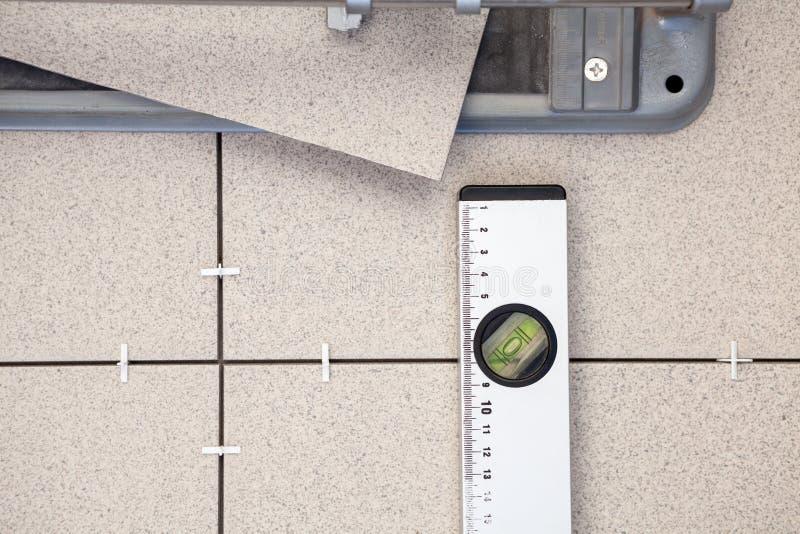 Κεραμίδι-κόπτης, επίπεδο οικοδόμησης για την επίστρωση κεραμιδιών, υπόβαθρο στοκ εικόνες