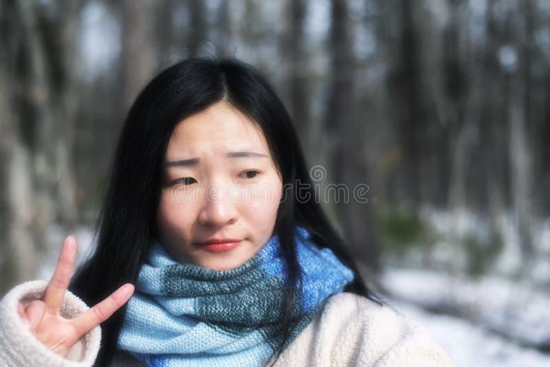 Κινεζική γυναίκα που λάμπει ένα σημάδι ειρήνης στοκ φωτογραφία