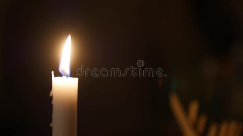 Κινηματογράφηση σε πρώτο πλάνο της φλόγας κεριών στο μαύρο υπόβαθρο, κάποιος που κινείται πίσω από το κερί στοκ εικόνες