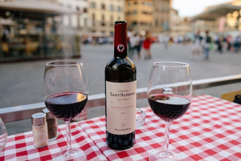 Κινηματογράφηση σε πρώτο πλάνο του κόκκινου κρασιού Sant Alfonso Chianti Classico και γυαλιά μπουκαλιών στον πίνακα στοκ φωτογραφίες με δικαίωμα ελεύθερης χρήσης