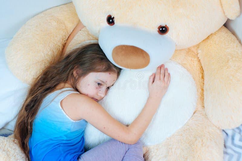 Κινηματογράφηση σε πρώτο πλάνο του χαριτωμένου λυπημένου μικρού κοριτσιού κοντά στη teddy αρκούδα Ιός Varicella ή Chickenpox αναφ στοκ εικόνα με δικαίωμα ελεύθερης χρήσης