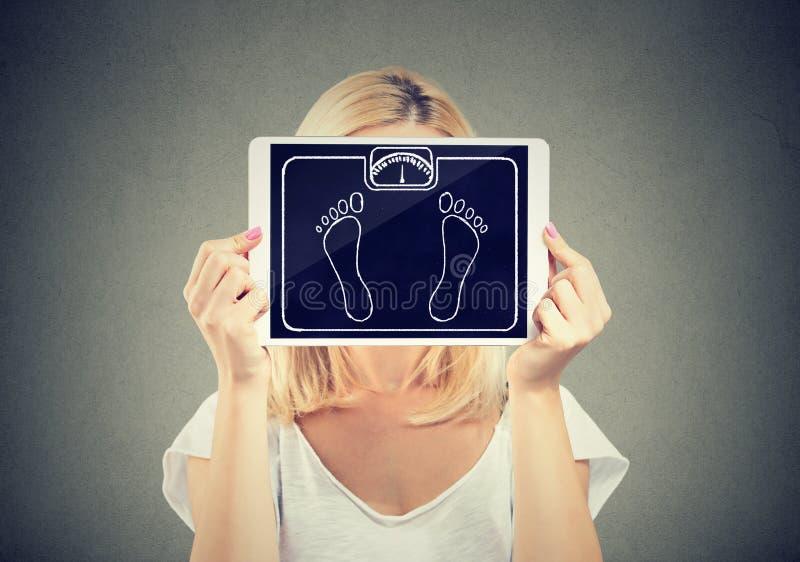 Κλίμακα βάρους ταμπλετών εκμετάλλευσης γυναικών μπροστά από το πρόσωπό της στοκ εικόνες