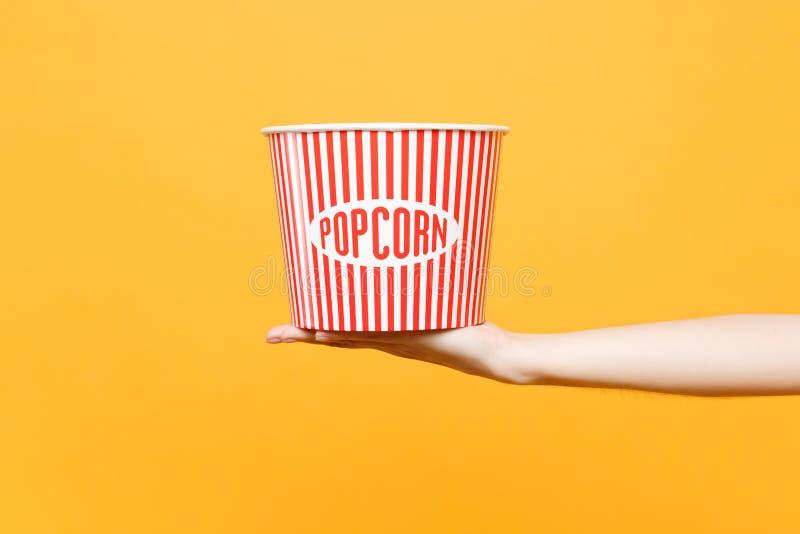 Κλείστε επάνω θηλυκό κλασικό σαφή κενό ριγωτό XL κάδο λαβής υπό εξέταση για popcorn που απομονώνεται στο τείνοντας κίτρινο πορτοκ στοκ φωτογραφία με δικαίωμα ελεύθερης χρήσης