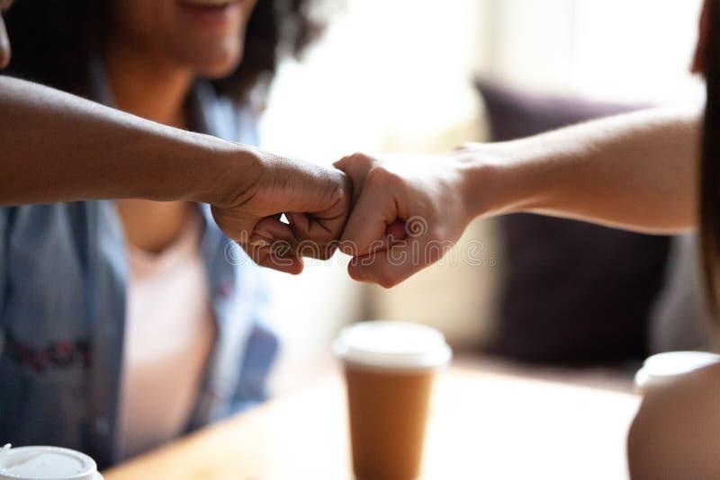 Κλείστε επάνω την πολυφυλετική πρόσκρουση πυγμών φίλων, γιορτάστε την επιτυχία στον καφέ στοκ εικόνες