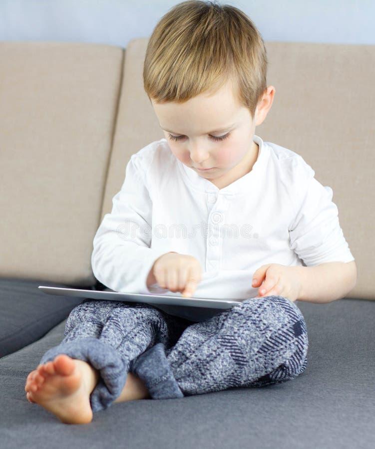 Κλείστε επάνω τη χαριτωμένη έξυπνη συνεδρίαση μικρών παιδιών στον καναπέ στο καθιστικό και τη χρησιμοποίηση της ταμπλέτας οθονών  στοκ φωτογραφίες με δικαίωμα ελεύθερης χρήσης