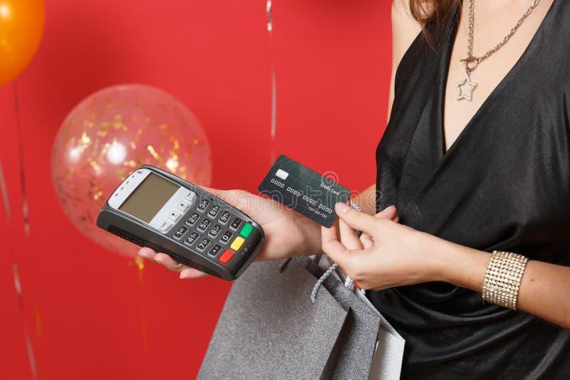 Κλείστε επάνω του ασύρματου σύγχρονου τερματικού πληρωμής τραπεζών λαβής κοριτσιών που επεξεργάζεται αποκτά τις πληρωμές με πιστω στοκ εικόνες