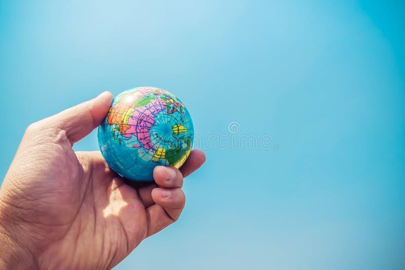 Κλείστε επάνω του χεριού επιχειρηματιών που παρουσιάζει μια μικρούς πρότυπους σφαίρα και μπλε ουρανό στοκ φωτογραφίες με δικαίωμα ελεύθερης χρήσης