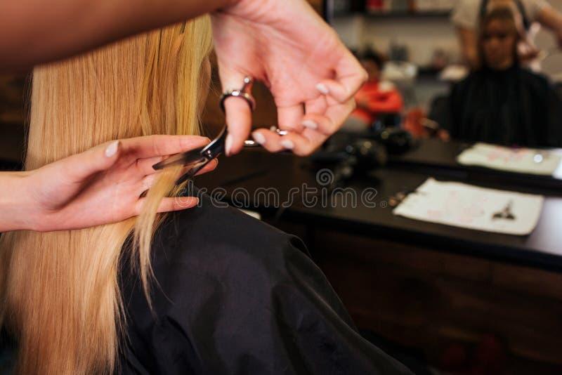 Κλείστε επάνω του χεριού κομμωτών κόβοντας την ξανθή τρίχα Να κάνει το νέο κούρεμα στο σαλόνι ομορφιάς στοκ εικόνες