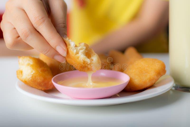Κλείστε επάνω το χέρι της γυναίκας που βυθίζει τα τηγανισμένα κουλούρια στο γλυκαμένο κορφολόγο ποτών στοκ φωτογραφία με δικαίωμα ελεύθερης χρήσης