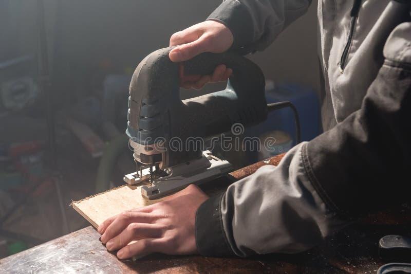 Κλείστε επάνω των χεριών του ξυλουργού που λειτουργούν τα εργαλεία δύναμης για το ξύλο Τορνευτικό πριόνι δύναμης στοκ φωτογραφία