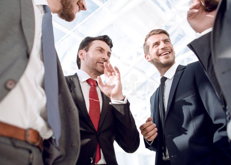 κλείστε επάνω φιλική επιχειρησιακή ομάδα που στέκεται στο γραφείο στοκ φωτογραφία