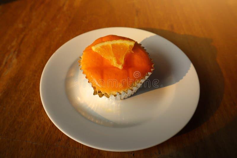 Κλείστε επάνω, πορτοκαλί κέικ μαρμελάδας, όμορφο χρώμα, εύγευστος, ευώδης και εύγευστος στο πιάτο πρωινού στοκ φωτογραφία