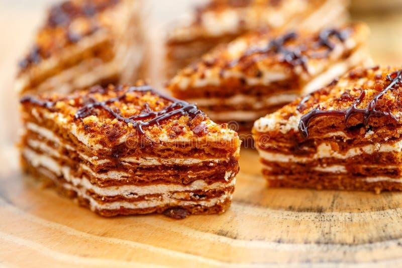 Κομμάτια του κέικ με τα στρώματα της κρέμας στον καμβά σε έναν ξύλινο πίνακα στοκ εικόνα