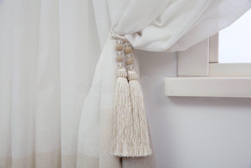 Κομψή κουρτίνα παραθύρων με το tieback στο δωμάτιο στοκ φωτογραφία με δικαίωμα ελεύθερης χρήσης