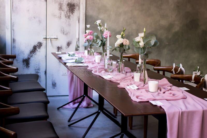 Κομψός σκοτεινός ρόδινος πίνακας γαμήλιου συμποσίου με τη διακόσμηση γυαλιών και λουλουδιών στο εσωτερικό στο εστιατόριο στοκ εικόνες με δικαίωμα ελεύθερης χρήσης