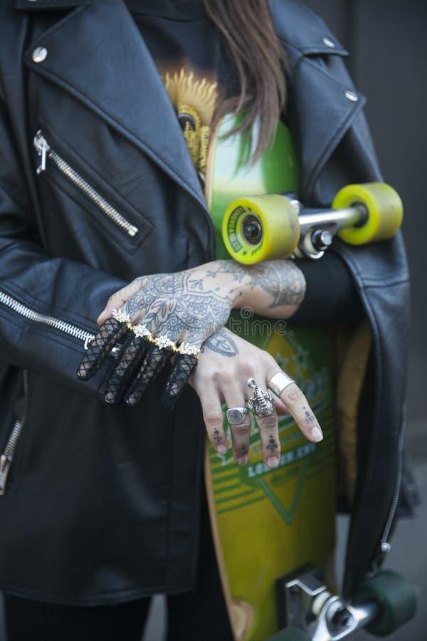 Κορίτσι με μια δερματοστιξία στο πρόσωπό της και χέρια με skateboard στα χέρια της και ένα μαύρο σακάκι δέρματος στοκ φωτογραφίες