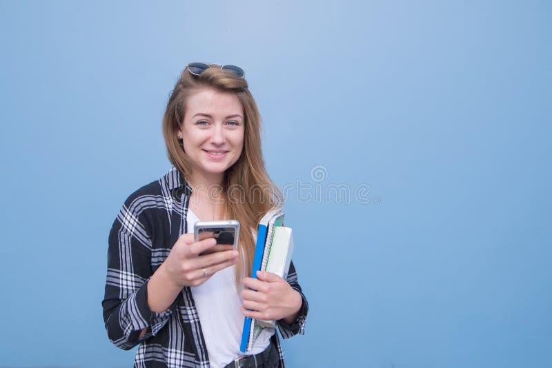 Κορίτσι σπουδαστών που απομονώνεται σε ένα μπλε υπόβαθρο με τα βιβλία, τα σημειωματάρια και ένα smartphone στα χέρια της που εξετ στοκ εικόνες