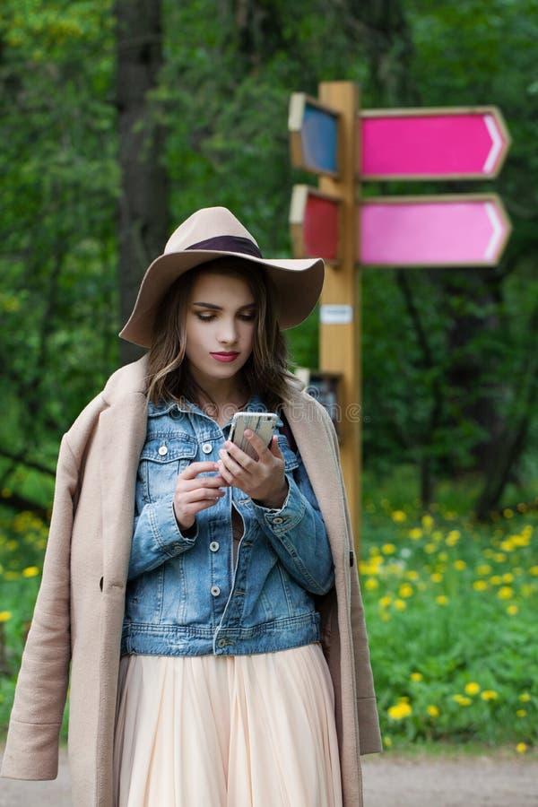 Κορίτσι τουριστών που συμβουλεύεται το ΠΣΤ για το έξυπνο τηλέφωνο σε μια τουριστική θέση υπαίθρια στοκ εικόνες με δικαίωμα ελεύθερης χρήσης