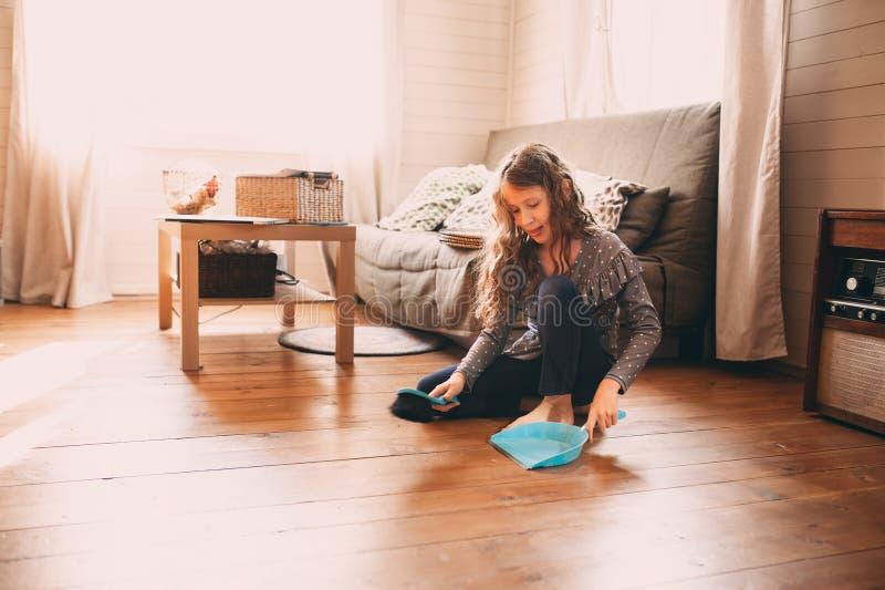 κορίτσι παιδιών που βοηθά με τα οικιακά και το καθαρίζοντας ξύλινο πάτωμα στο σπίτι στοκ φωτογραφία με δικαίωμα ελεύθερης χρήσης