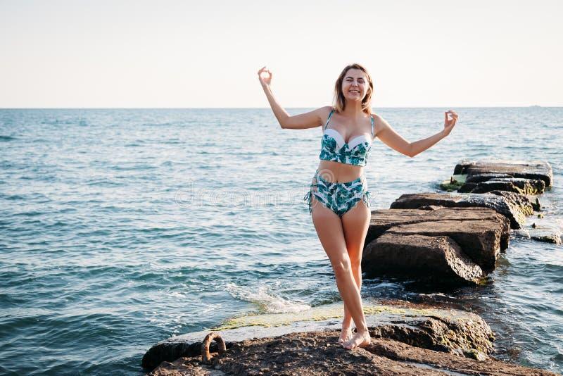 Κορίτσι που κάνει τη γιόγκα στην παραλία, στο χρόνο ηλιοβασιλέματος Υγιής τρόπος ζωής στοκ εικόνες