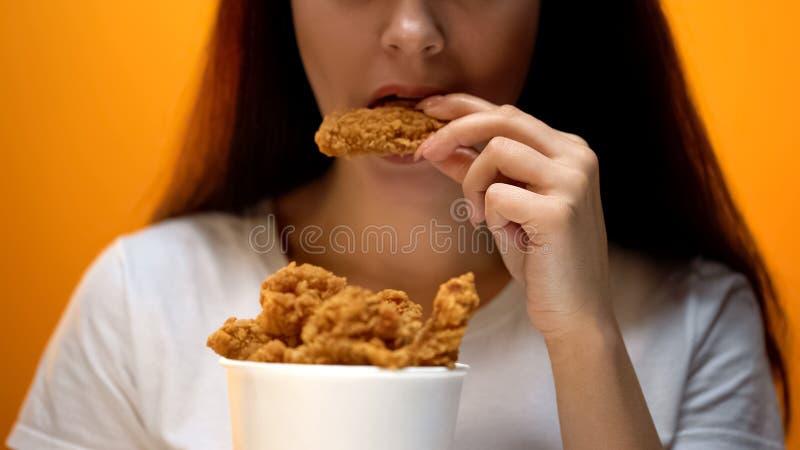 Κορίτσι που τρώει τα φτερά κοτόπουλου, τα υψηλά τρόφιμα θερμίδας και τους κινδύνους για την υγεία, χοληστερόλη στοκ εικόνα