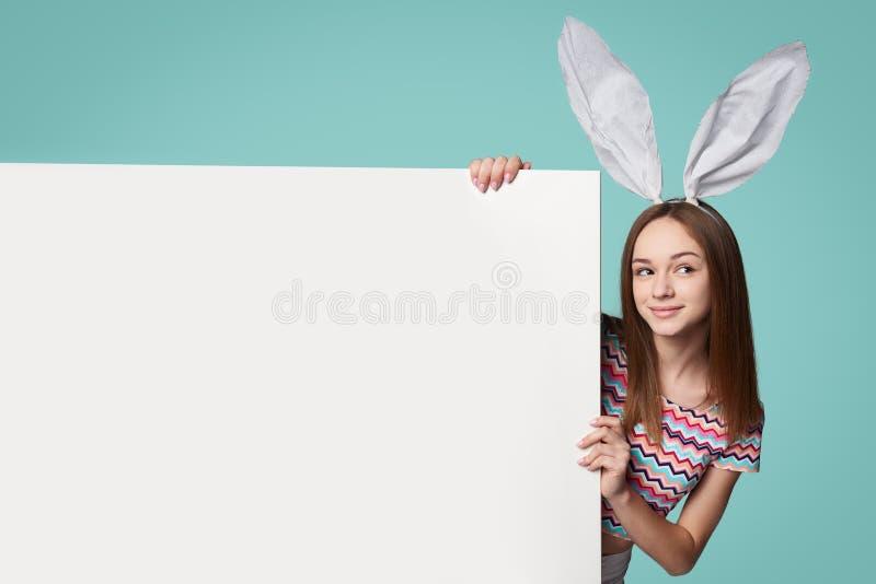 Κορίτσι που φορά τα αυτιά λαγουδάκι που κρατούν ένα έμβλημα στοκ εικόνες