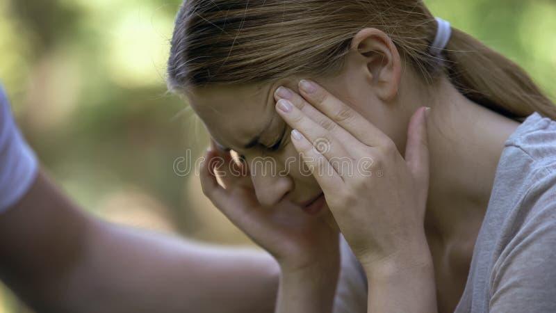 Κορίτσι που υφίσταται τον οξύ πονοκέφαλο, που ανησυχεί για τις αποτυχίες, αρσενικό χέρι που ανακουφίζουν την στοκ εικόνες με δικαίωμα ελεύθερης χρήσης