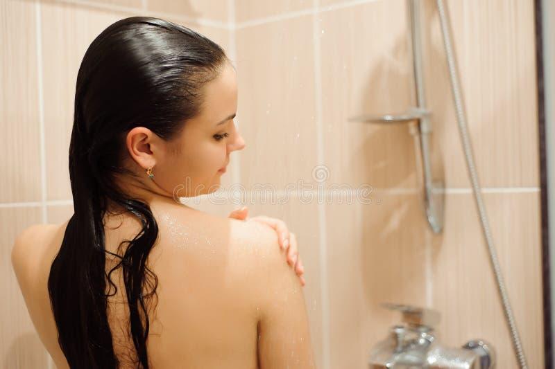 Κορίτσι που πλημμυρίζει στην περίφραξη θαλαμίσκων καμπινών ντους Νέα γυναίκα που φροντίζει την υγιεινή στο λουτρό στοκ φωτογραφία