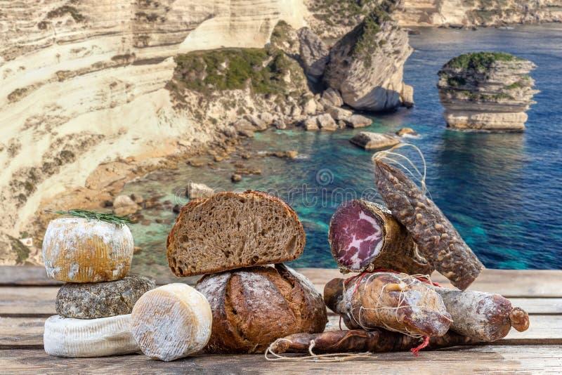 Κορσικανικές ειδικότητες: οι λιχουδιές, και το τυρί έκαναν στην Κορσική με το υπόβαθρο πανοράματος απότομων βράχων κόλπων veccio  στοκ εικόνες με δικαίωμα ελεύθερης χρήσης
