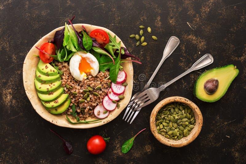 Κουάκερ φαγόπυρου με το βρασμένους αυγό, το αβοκάντο, το ραδίκι, chard τα φύλλα, το arugula, τις ντομάτες και τους σπόρους Κύπελλ στοκ εικόνες
