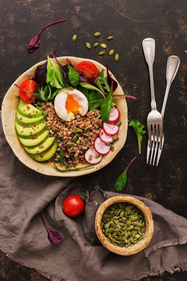 Κουάκερ φαγόπυρου με το βρασμένους αυγό, το αβοκάντο, το ραδίκι, chard τα φύλλα, το arugula, την ντομάτα και τους σπόρους Κύπελλο στοκ φωτογραφία με δικαίωμα ελεύθερης χρήσης