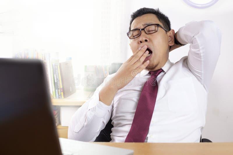 Κουρασμένος νυσταλέος ασιατικός επιχειρηματίας που έχει καταπονημένο στοκ εικόνα