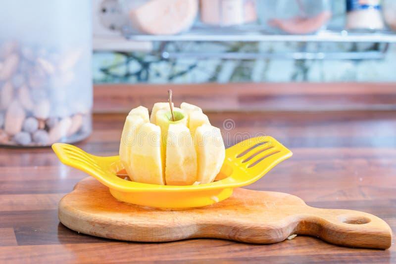 Κοπή του μήλου στις φέτες με μια ειδική συσκευή στοκ εικόνες