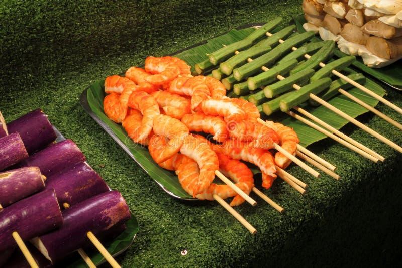 Κρέας γαρίδων στα ξύλινα οβελίδια για το ψήσιμο στη σχάρα στο αντίθετο κατάστημα στοκ εικόνα