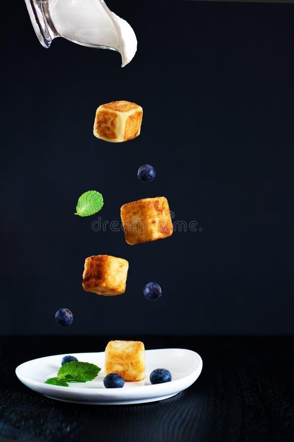 Κύβοι τυριών εξοχικών σπιτιών, πιατάκι με τα βακκίνια κρέμας και minl τα φύλλα που αφορούν κάτω το άσπρο πιάτο, πιατάκι με την κρ στοκ φωτογραφία