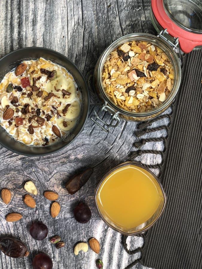 Κύπελλα καταφερτζήδων Muesli βρωμών superfoods που ολοκληρώνονται με την μπανάνα, νιφάδες καλαμποκιού, αμύγδαλο, granola με το χυ στοκ εικόνα με δικαίωμα ελεύθερης χρήσης