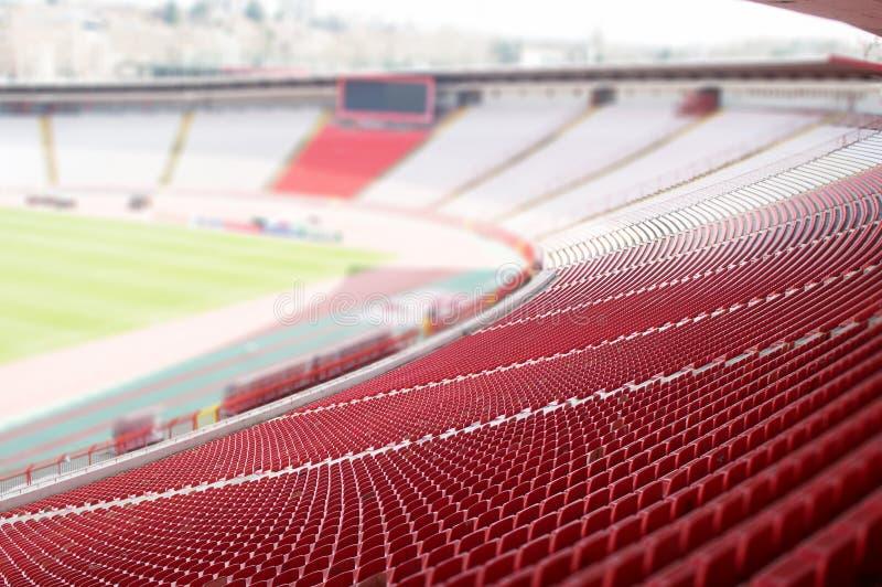 Κόκκινα καθίσματα στο στάδιο στοκ φωτογραφία