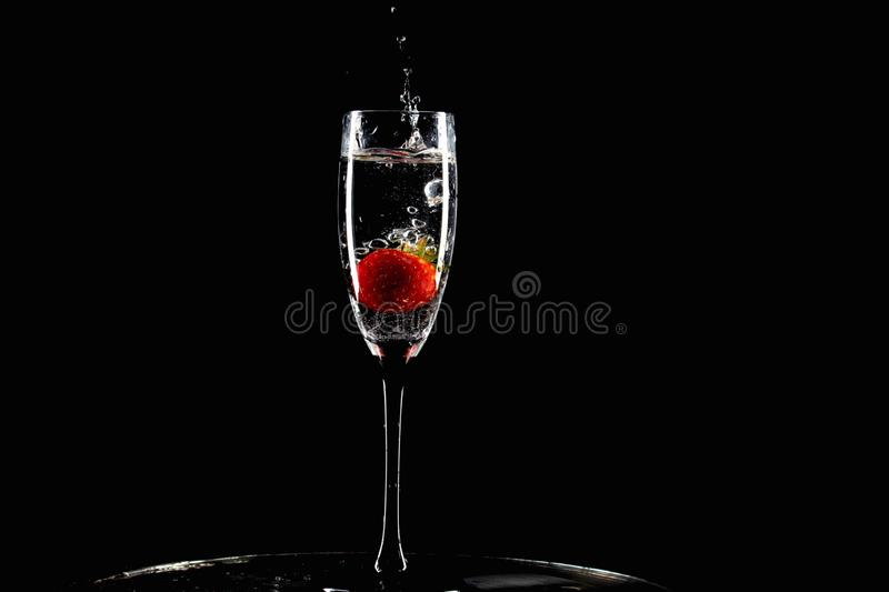 Κόκκινες πτώσεις φραουλών σε ένα ποτήρι του νερού με τον παφλασμό στοκ εικόνα