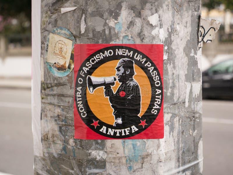 Κόκκινη αυτοκόλλητη ετικέττα Antifa σε μια θέση λαμπτήρων στο Πόρτο, Πορτογαλία στοκ φωτογραφία με δικαίωμα ελεύθερης χρήσης